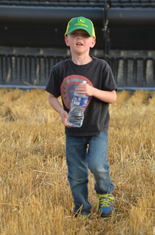 All this little boy needs is a field of wheat, a combine and a bottle of water.